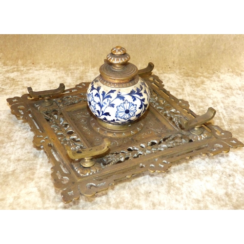 710 - A Square Brass Ink Stand having pierced and scalloped decoration, centre china and bulbous inkwell w...