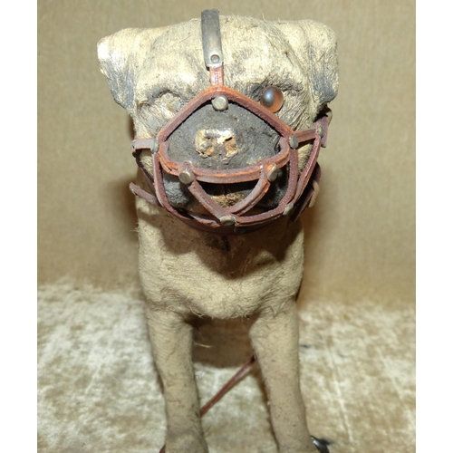 714 - A Child's Papier Mache Model of a Dog wearing a muzzle on wheels, 26cm long, 19.5 cm high (1 wheel a...