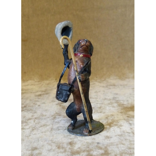 727 - A Cold Painted Metal Figure of a standing dog holding a top hat, binoculars and walking cane, 10cm h...