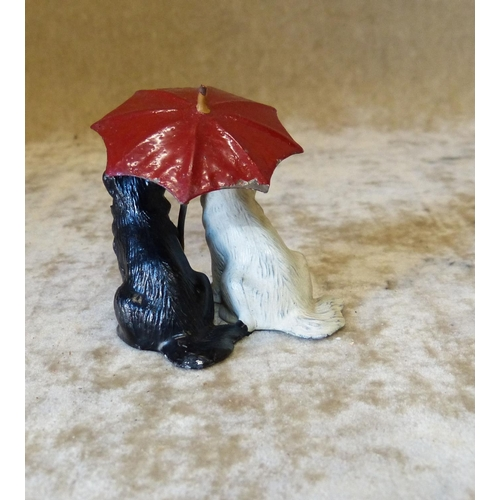 728 - A Painted Metal Group of 2 Seated Dogs under an umbrella, 6cm high...