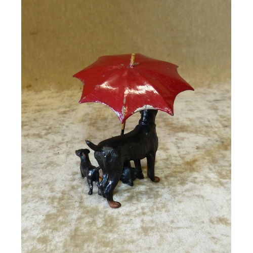 729 - A Painted Metal Group of 3 Dogs under umbrella (smallest dog front leg missing) 9.5cm high...