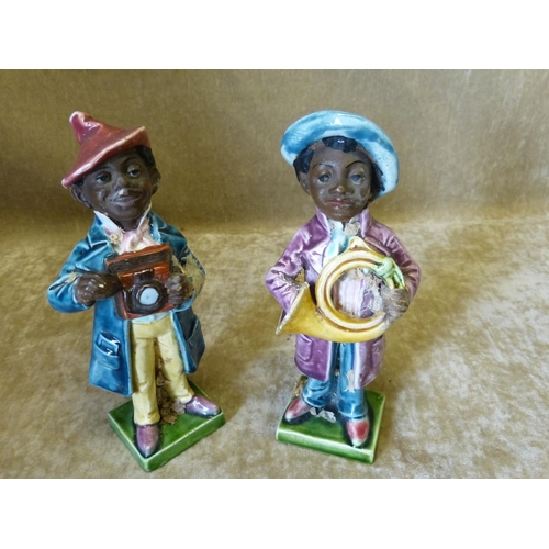 77 - 2 Glazed Earthenware Figures of African Boys with trumpet and camera on square bases, 16cm high...