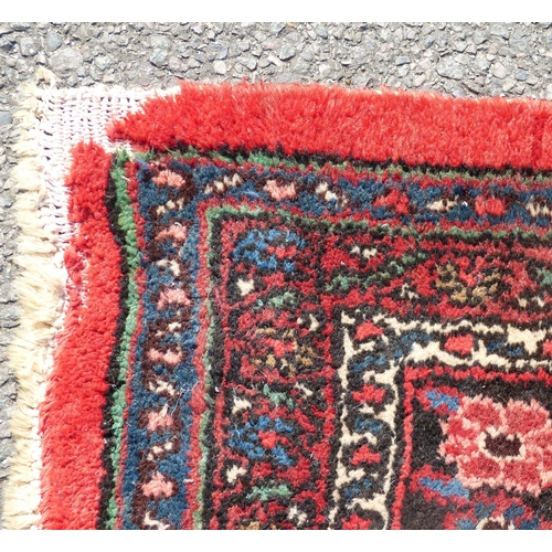 801 - A Persian Carpet on red and blue ground having centre medallion (circular damage on rim and in 1 cor...