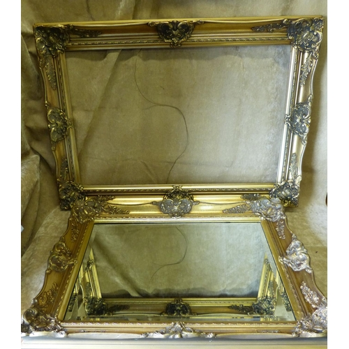 816 - A Gilt Hanging Modern Bevelled Wall Mirror with raised floral and scroll rim, 77cm wide, also a simi...