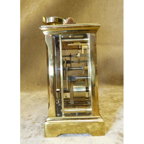 846 - A Brass Carriage Clock having swing overhead handle, white enamel dial with Roman numerals, 12cm hig...