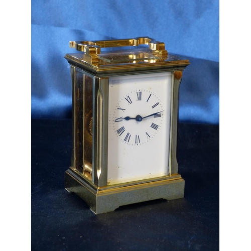 847 - A Brass Carriage Clock having chamfer corners, white enamel dial with Roman numerals, swing overhead...