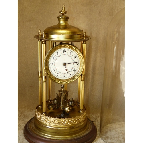 856 - A Gilt Metal Anniversary Clock having glass dome, reeded column supports (pendulum wire in need of r...