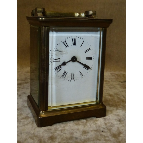 859 - A Small Glass Carriage Clock having white enamel dial, with Roman numerals and swing overhead handle...
