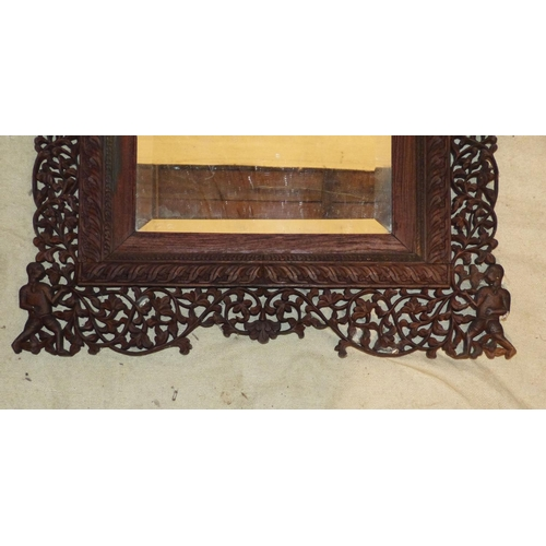909 - An Eastern Carved Hanging Bevelled Wall Mirror with all over pierced, floral, figure and scroll deco...