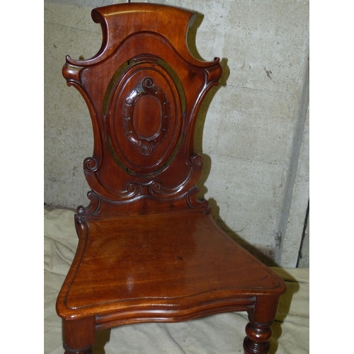 911 - A Victorian Mahogany Shield Back Hall Chair having carved scroll decorations, slid seat on round tur...
