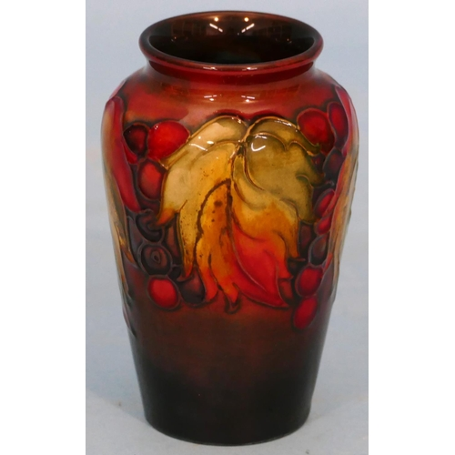 41 - A Moorcroft Small Round Bulbous Thin Necked Vase on blue and brown ground having multicoloured berry...