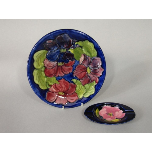 10 - A Moorcroft blue ground plate with red and purple clematis pattern decoration and with paper label t...