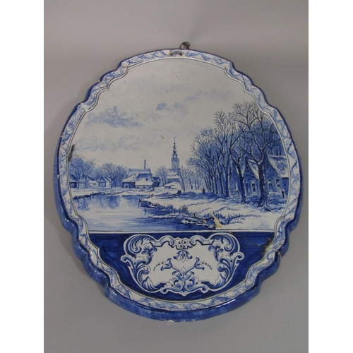 28 - A 19th century Delft plaque of shaped oval form with painted winter canal scape and with painted mar...