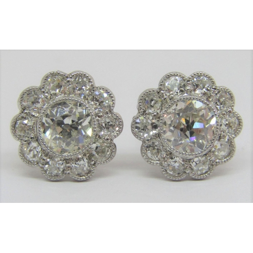 281 - Fine pair of diamond daisy cluster stud earrings,millegrain set in unmarked white metal,central ston...