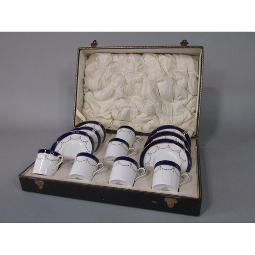 53 - A cased set of six Aynsley coffee cans and saucers with blue and gilt decoration and with printed Ha...