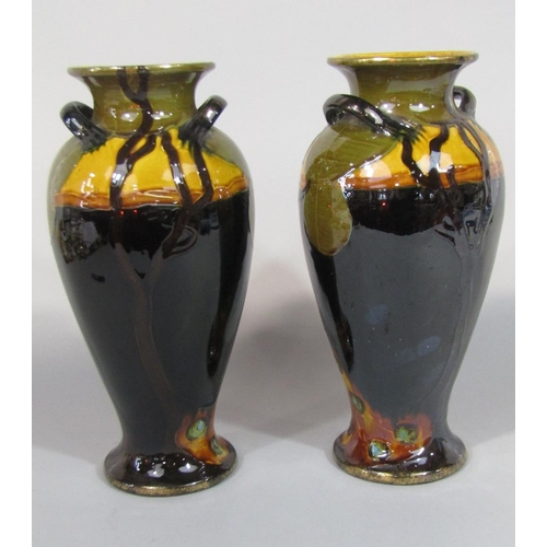 56 - A pair of Phoenix ware two handled vases,with painted and gilded peacock decoration and printed mark...