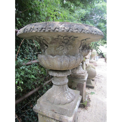27 - A pair of good quality weathered reconstituted fluted urns raised upon square cut bases, 52