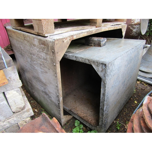Three large galvanised iron water tanks, one with riveted detail, 125cm wide and smaller