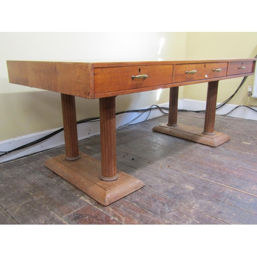 1515 - An unusual light oak library table, the rectangular top fitted with three frieze drawers raised on f...
