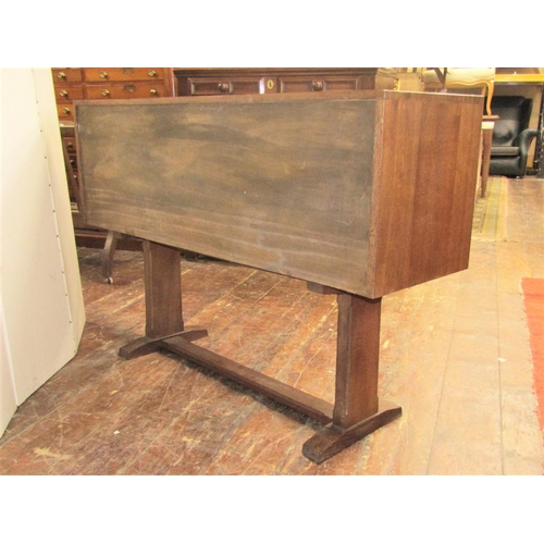 1517 - A small Cotswold School oak sideboard with exposed dovetail construction and enclosed by a pair of s...