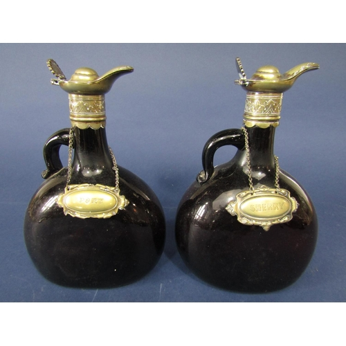 A pair of antique brown glass flask decanters with silver plated lids and scallop shell thumb piece with sherry and port decanter labels, the bottles 22cm high (2)