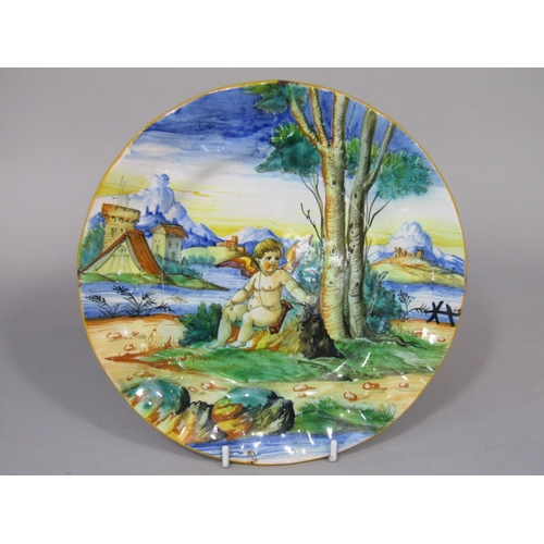 657 - A continental tin glazed earthenware plate with polychrome painted decoration of a cupid in a landsc...
