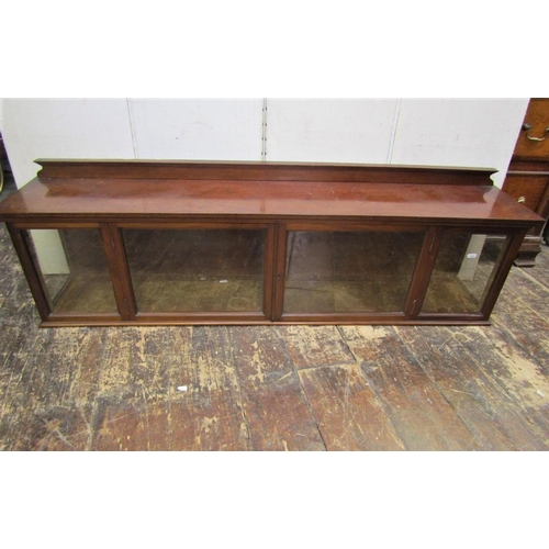 A 19th century mahogany cabinet of horizontal form, enclosed by a pair of glazed panelled doors and further glazed panels to three sides, velvet lined and with raised back, 138cm long x 35cm high
