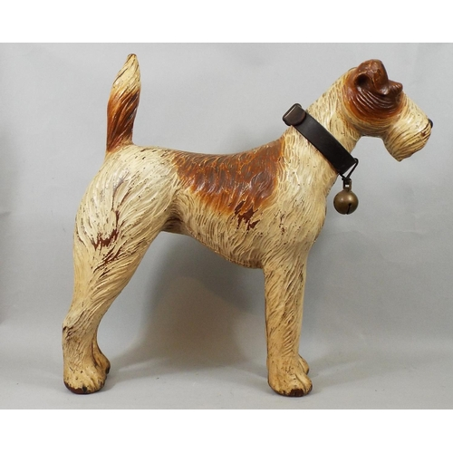 25 - A vintage moulded figure of a terrier with leather collar and brass bell, 46 cm in height...