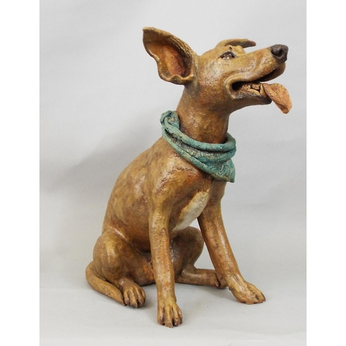 48 - A studio pottery figure of a terrier wearing a scarf, in seated pose, by Joanna Cooke, 32cm high...