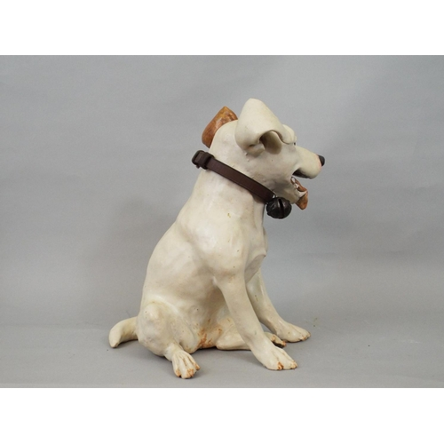 53 - A studio pottery figure of a seated terrier by Joanna Cooke, 26cm high...