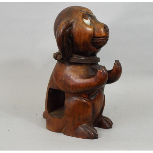 55 - A vintage googly eyed carved timber dog supporting two clothes brushes, 25cm high...
