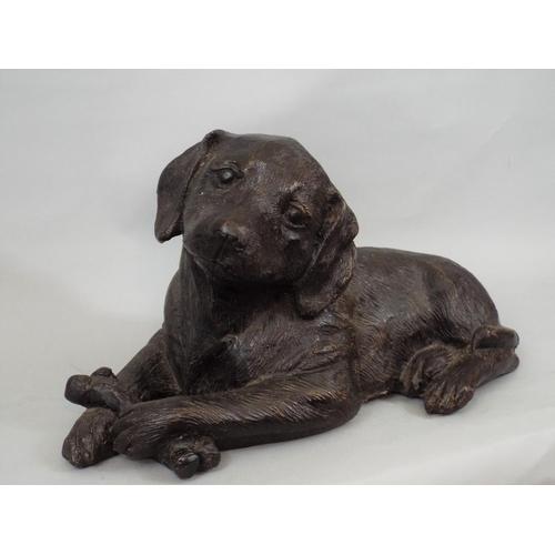 60 - A bronze model of a puppy holding a bone, 20cm approx...