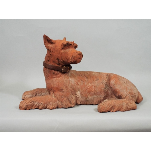7 - A Victorian terracotta figure of a recumbent terrier with later leather collar, 36 cm in length...
