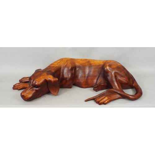 A good carved hardwood figure of a recumbent hound, 64cm long