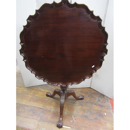 A Georgian style snap top table with pie-crust border, carved and foliated column further carved tripod base with claw and ball supports, 75 cm diameter