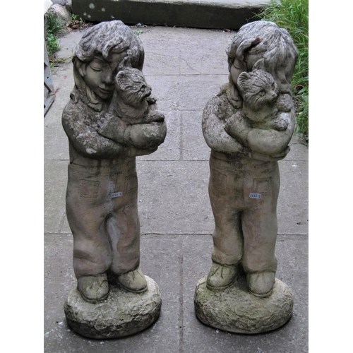 A matched pair of contemporary but partially weathered cast composition stone garden ornaments in the form of standing girl figures cuddling kittens, 68 cm high