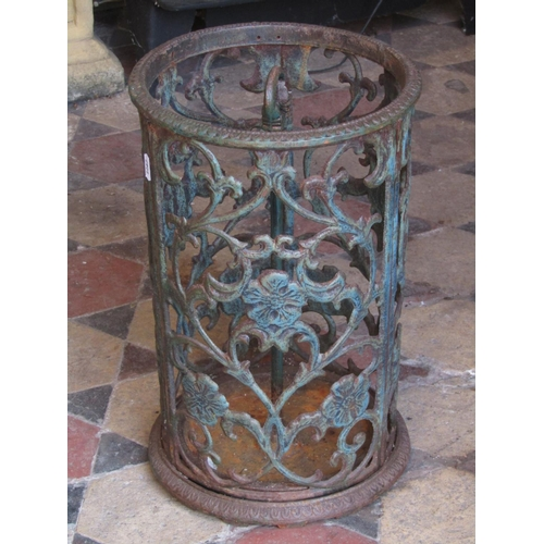 2098 - A cast iron umbrella stand of cylindrical form with pierced scrolling foliate detail and removable d...
