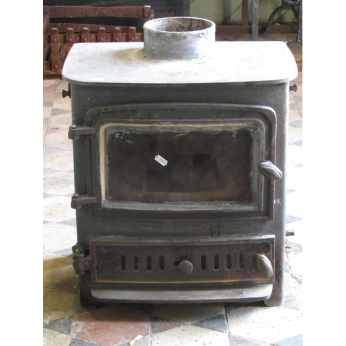 2099 - A cast iron stove enclosed by a rectangular and slightly arched glazed panelled door over a pierced ...