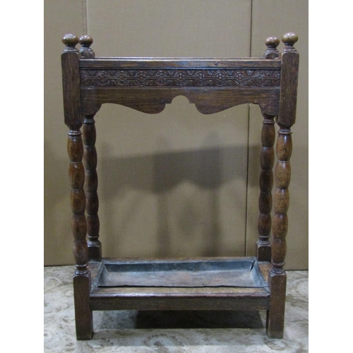 A 1920s oak three divisional umbrella/stickstand of rectangular form with turned bobbin supports and removable drip tray
