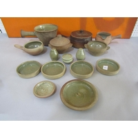 A collection of Leach type St Ives Pottery celadon glazed cookware comprising two twin handled bowls (af) one with lid, together with three single handled pots, one with a spout, another one with a lid, very small dish and four circular hors d'oeurves type dishes (10)