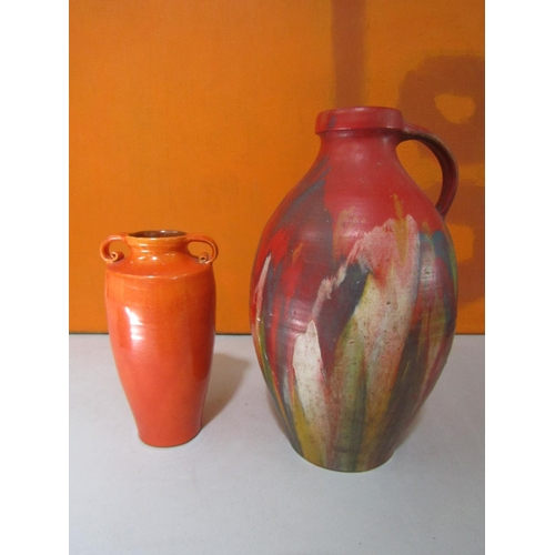 49 - Brannam of Barnstaple pottery - Studio pottery water carrying jug, with red lava type glaze with mot...