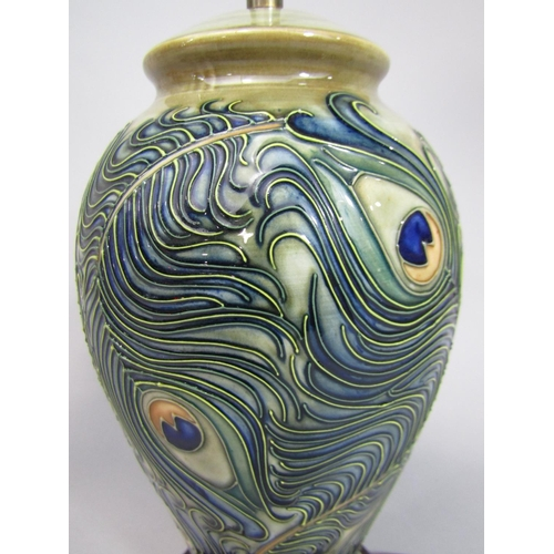 1007 - A Moorcroft ceramic lamp base, with painted and moulded peacock feather design in the art nouveau ma...