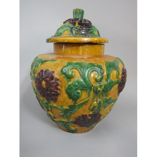 1018 - A large pottery vase and cover with ochre glaze and relief moulded decoration of trailing foliage an...