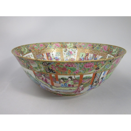 1045 - A 19th century Cantonese punch bowl with polychrome painted continuous decoration to the exterior in...