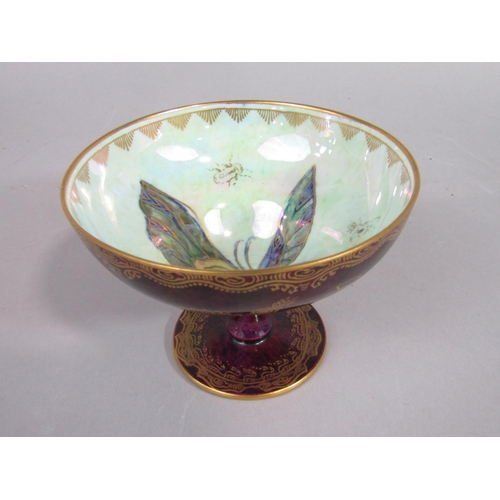 1052 - A Wedgwood lustre bowl raised on a circular foot, with dark red speckled glaze to the exterior in th...