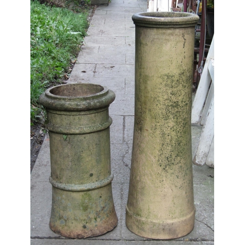 2022 - Two reclaimed buff coloured chimney pots of cylindrical form (varying design and height), the talles...