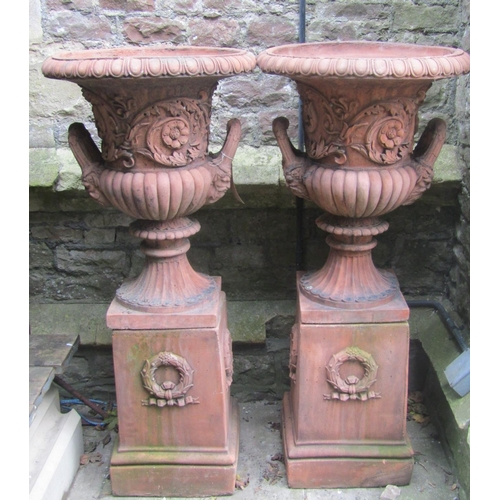 2026 - A pair of reproduction campana shaped garden urns with flared egg and dart rims, raised floral relie...