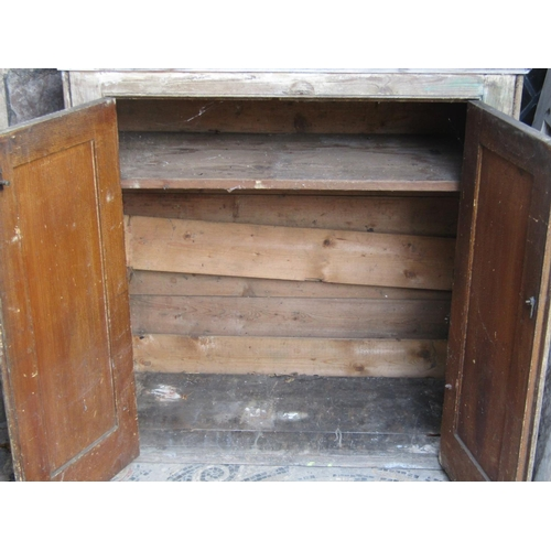 2032 - An old pine side cupboard enclosed by a  pair of rectangular moulded panelled doors flanked by furth...