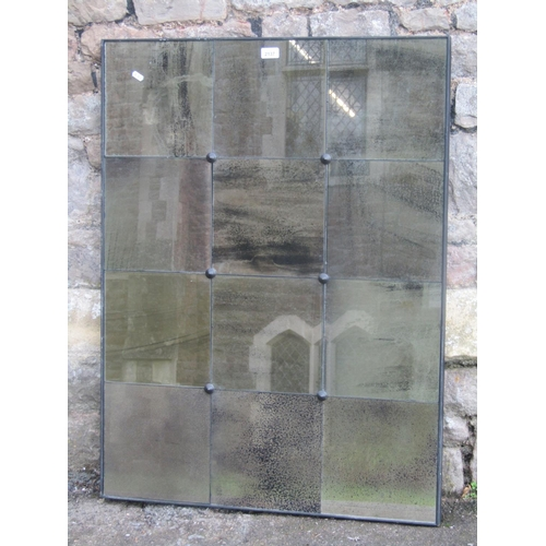 A contemporary wall mirror of rectangular form the simple ebonised frame enclosing 12 segmented simulated distressed glass plates, 101 cm x 76 cm