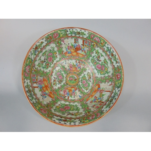 1058 - A late 19th century canton famille rose porcelain bowl, decorated with panels of figures and foliage...